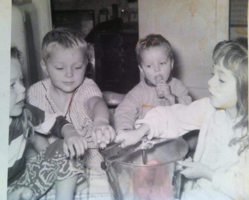 4 children mixing bread in a bucket