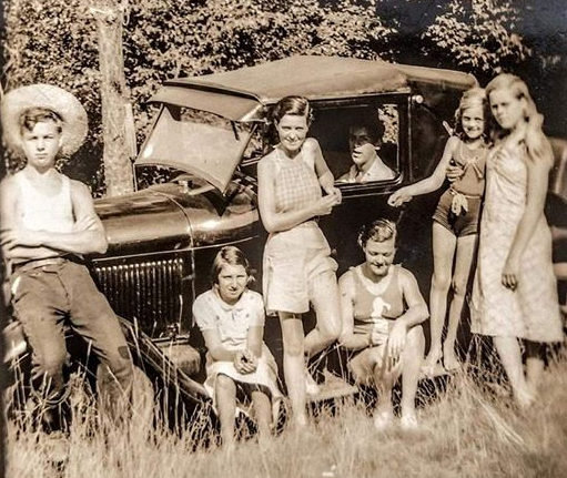 sepia toned portrait of family around a Model T