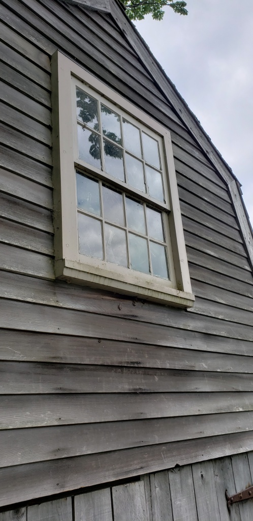 an old window in the side of a boat house
