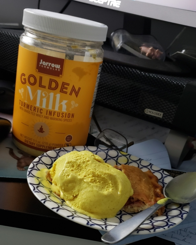 A jar of golden milk powder and a scoop of golden milk ice cream on a piece of cherry pie