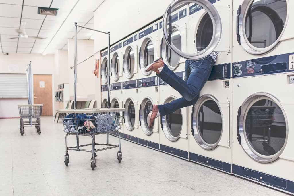 woman diving into a washing machine