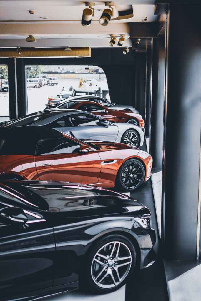 multiple high end cars parked in a garage.