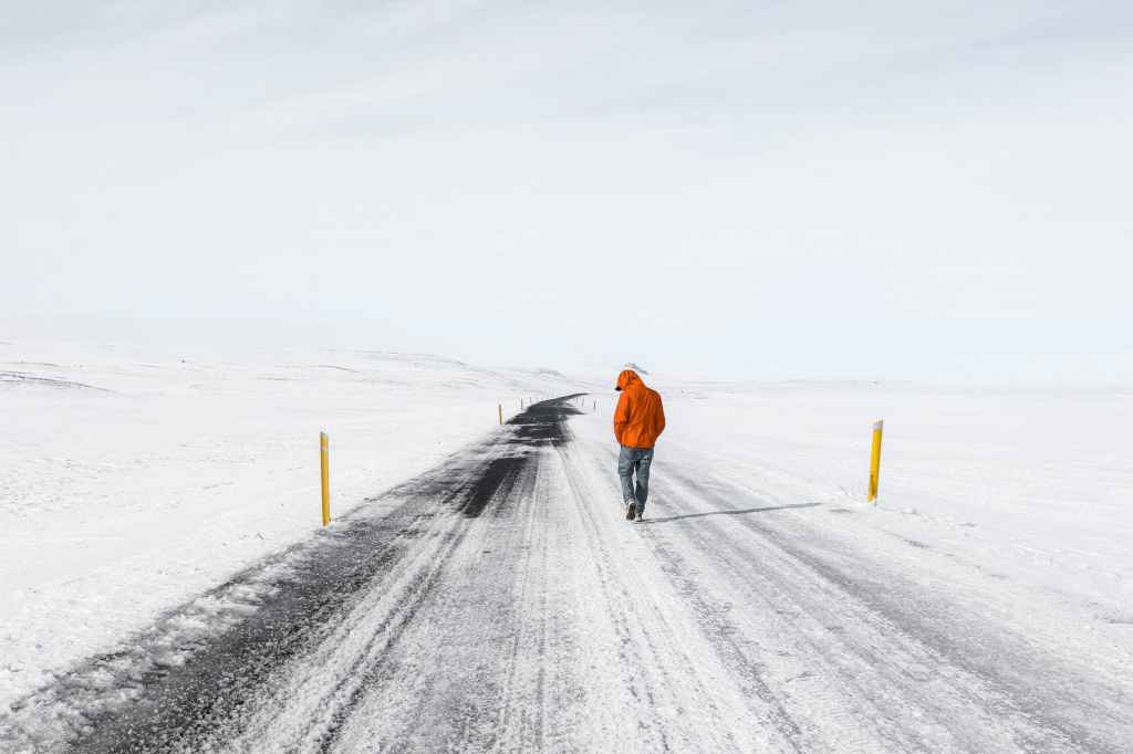 person walking down an empty highway in the snow