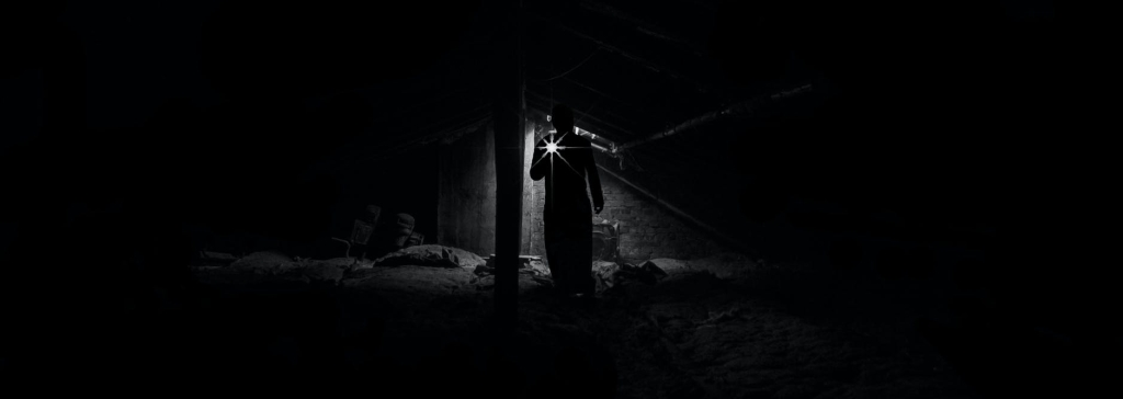 person in dark room with a flashlight
