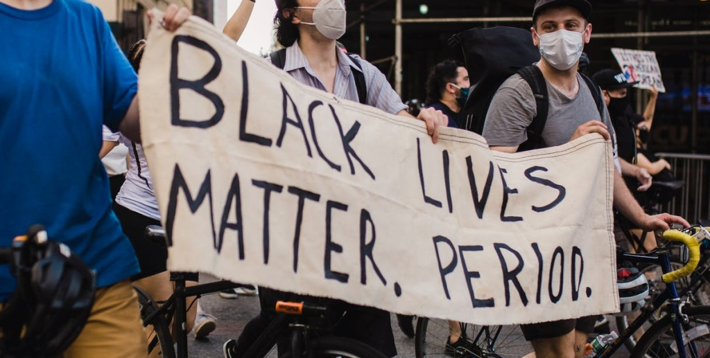 masked protesters carrying Black Lives Matter banner