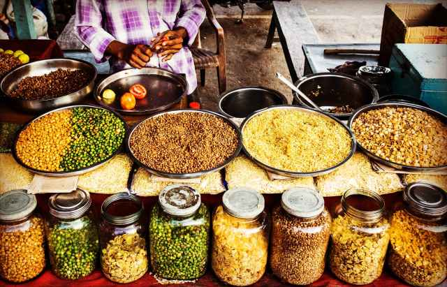 a spice market with pans of rice, beans, and other ingredients