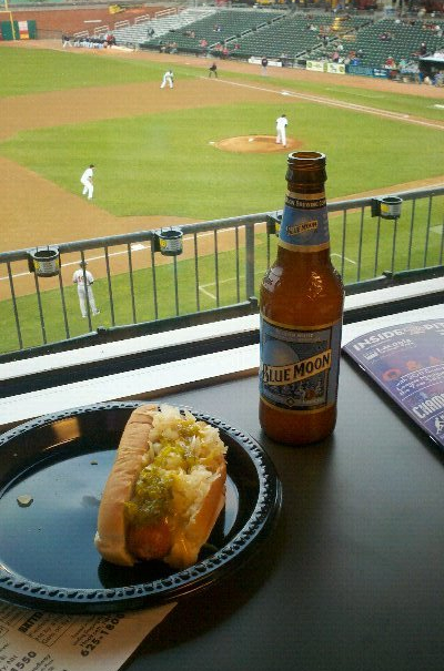 A beer and a loaded hot dog