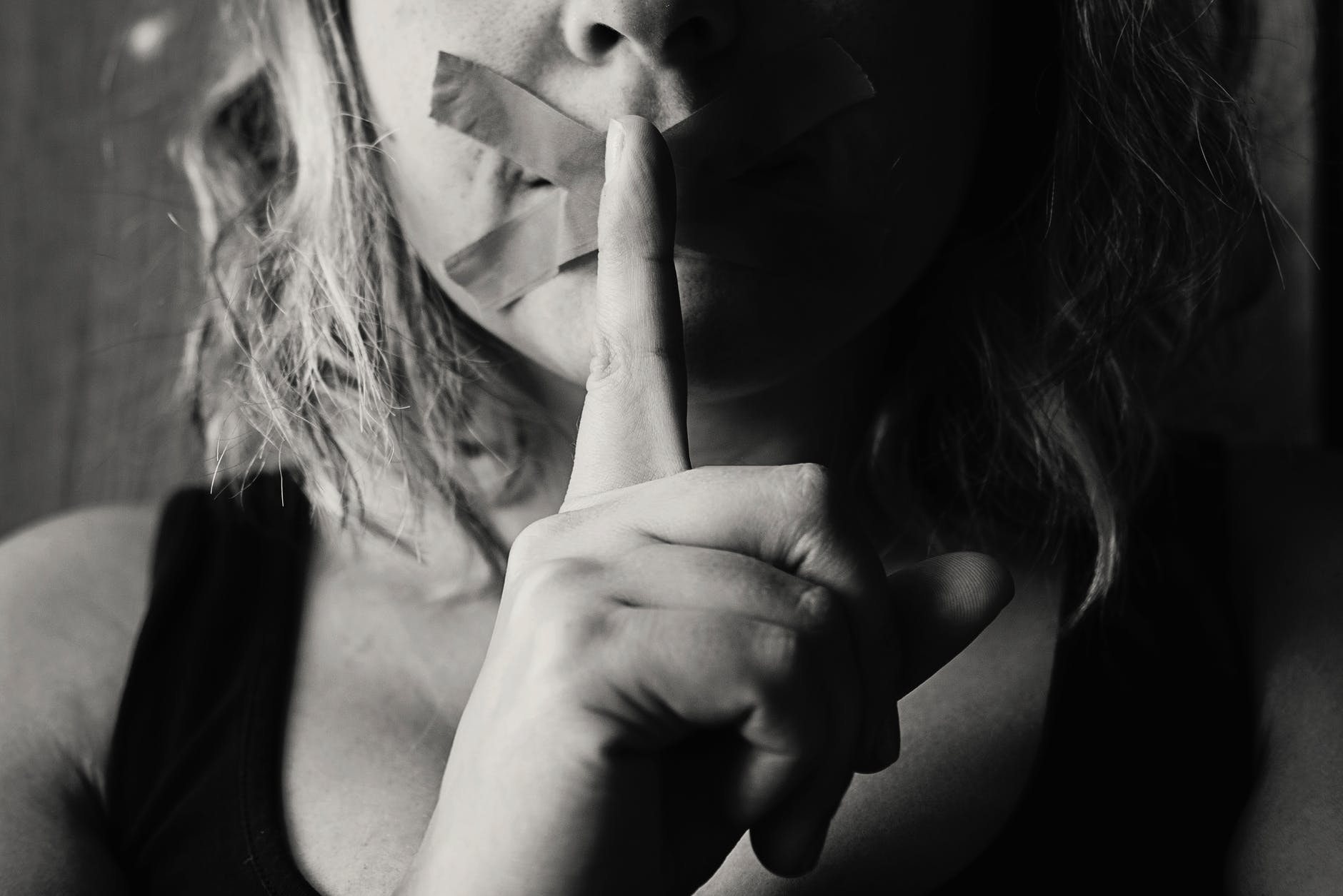 woman with tape over her mouth and finger to her mouth shushing