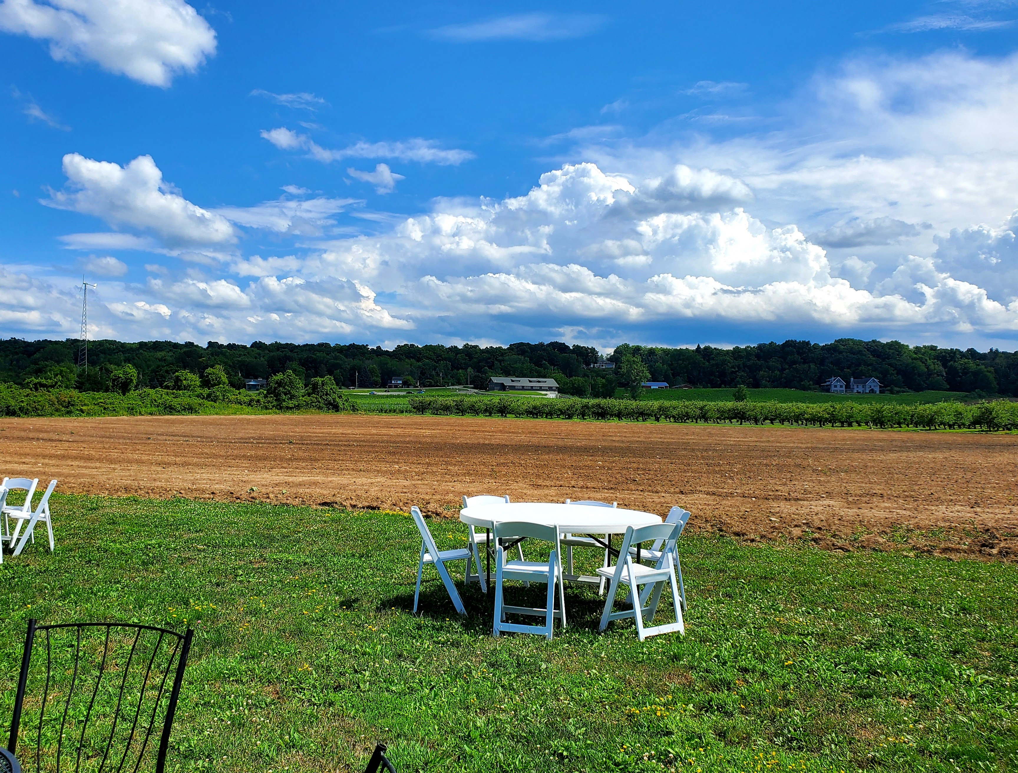Table and chairs overlooking tilled land and Arrowhead Winery in the distance