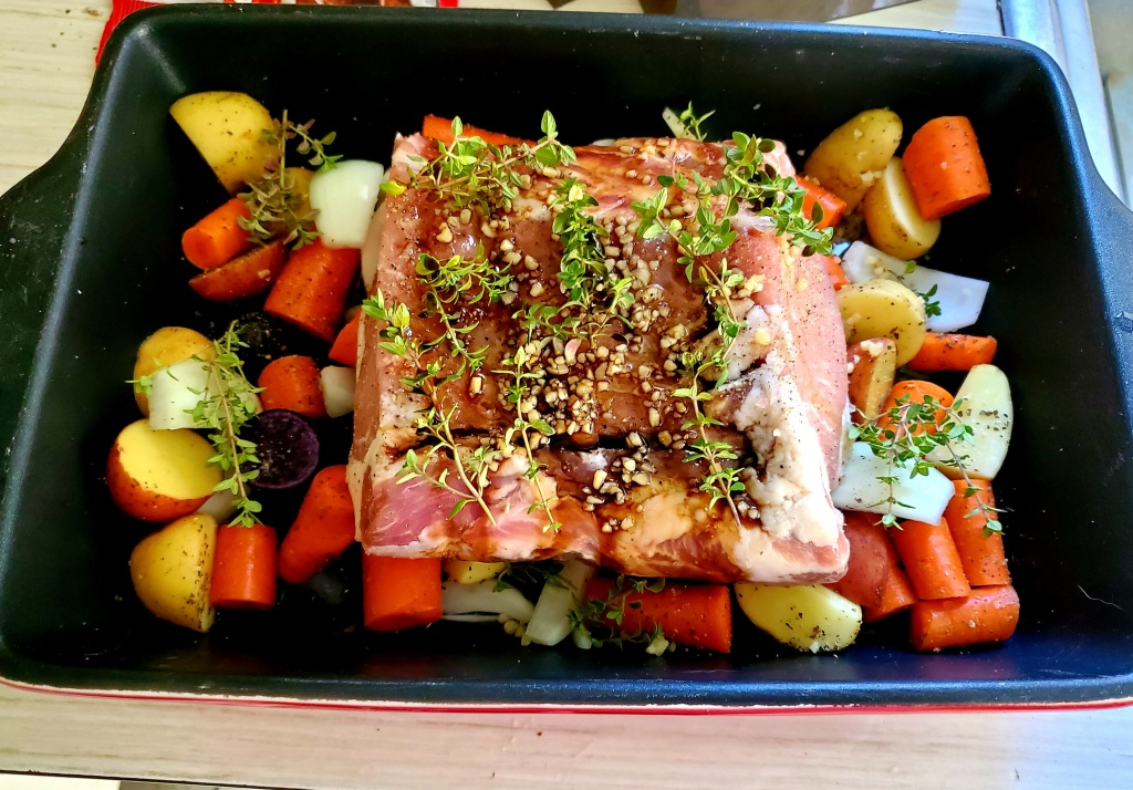 Pork roast on vegetables with herbs