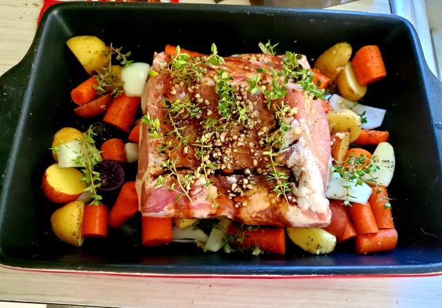 Pork roast on vegetables with herbs