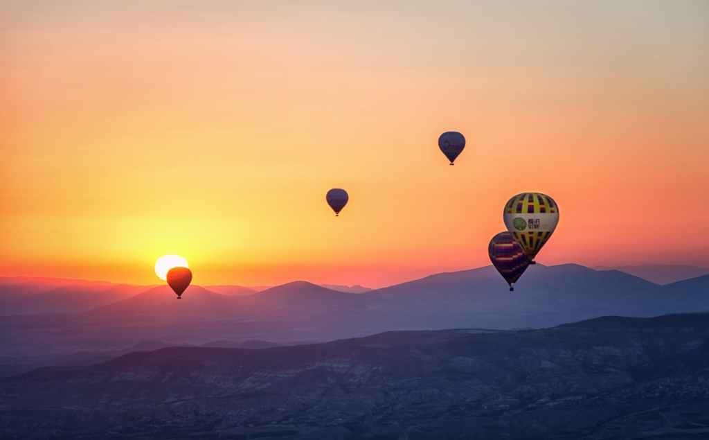 multiple hot air balloons at sunset