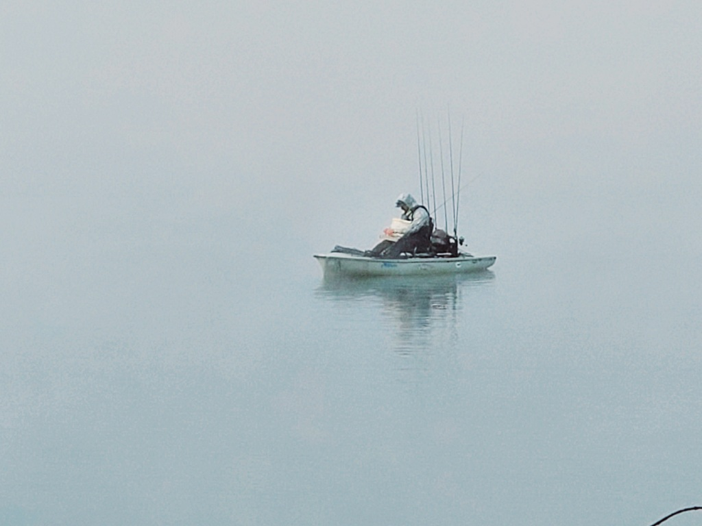 A lone fisherman out in a small boat with 7 fishing rods!