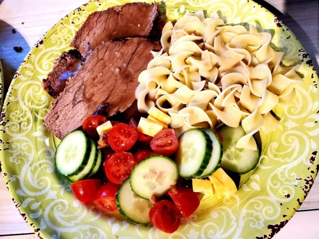 roast beef with gravy, noodles and a tomato and cucumber salad