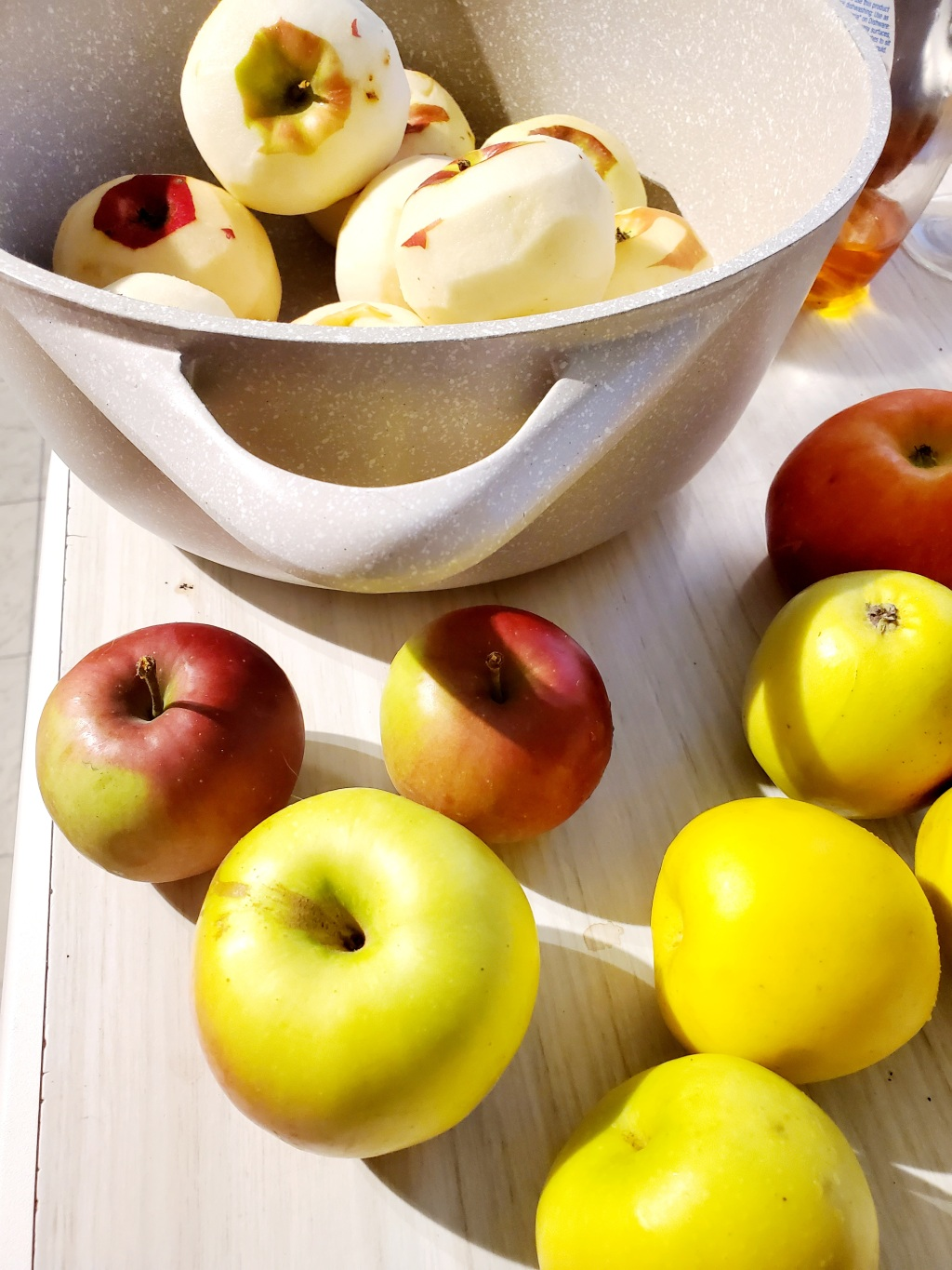 yellow and red apples and a pan filled with peeled apples