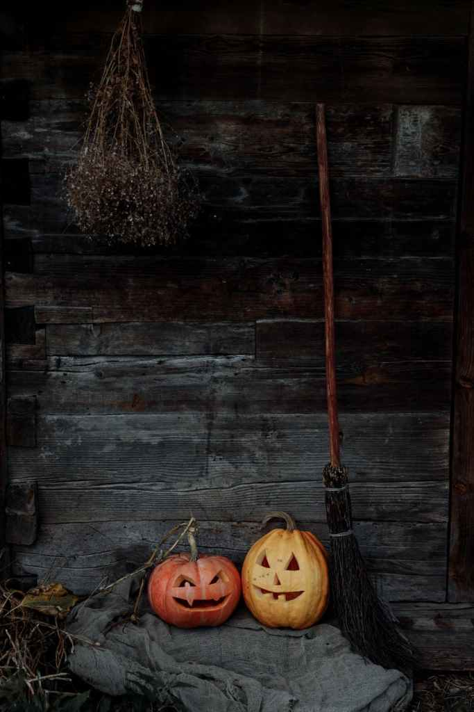 wooden wall with pumpkins and broom leaning