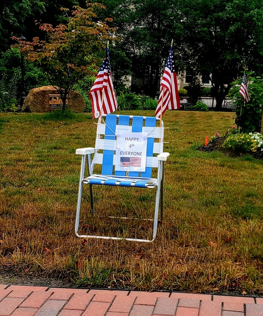 Blue and white folding chair decorated with flags.