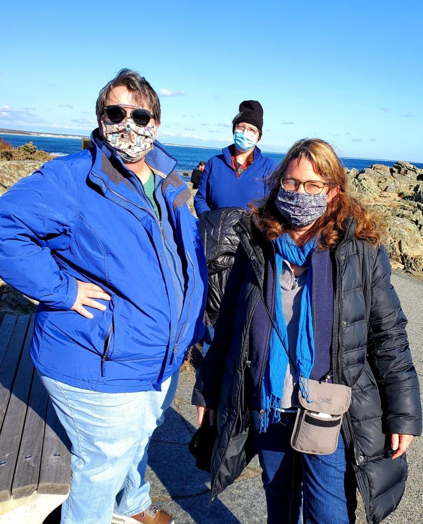 My 3 hiking companions dresses in warm layers, all in the same blue as the ocean