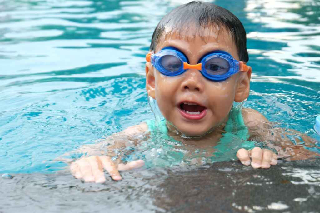 Small boy in a pool wearing goggles