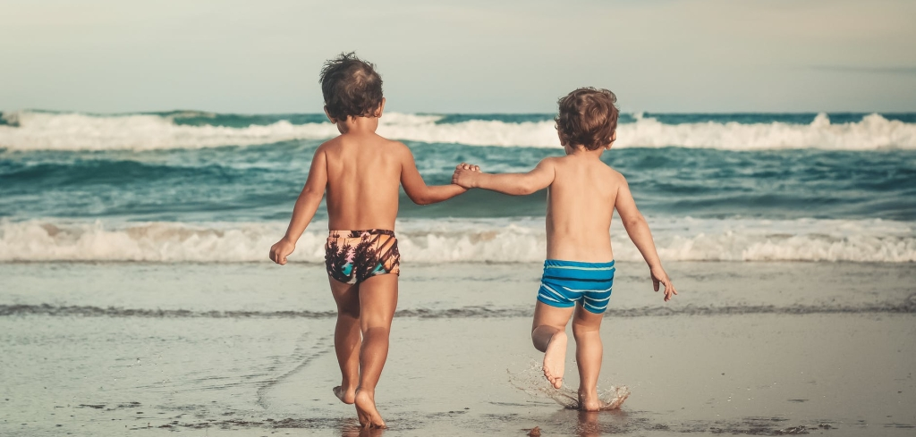 Two little boys walking towards the waves