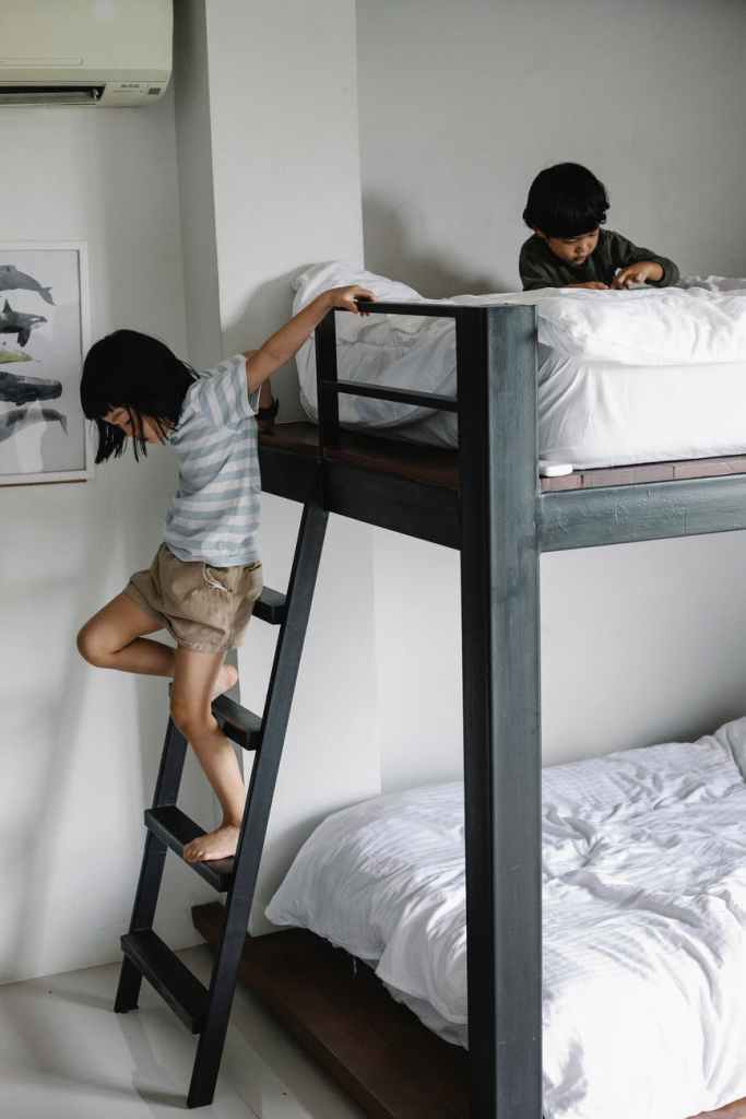 Girl climbing down ladder from bunk bed