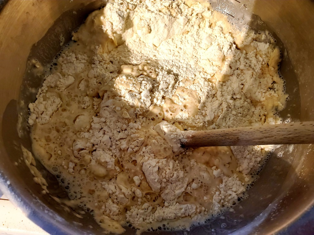Dry ingredients and water being mixed with a spoon