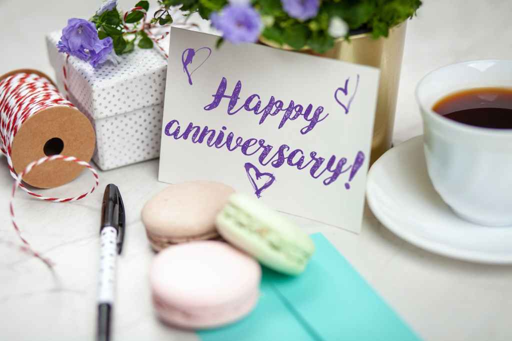 Cup of tea, three macarons, and a small gift box with a happy anniversary card