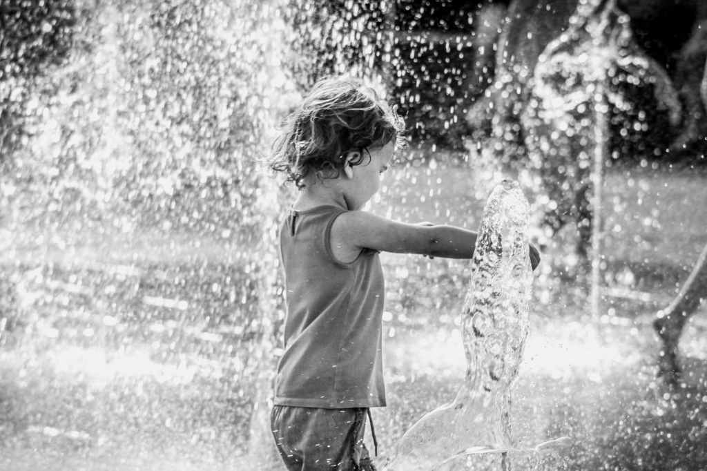 small child playing in a fountain