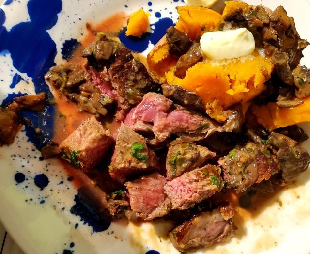 Steak cut up alongside buttered sweet potatoes