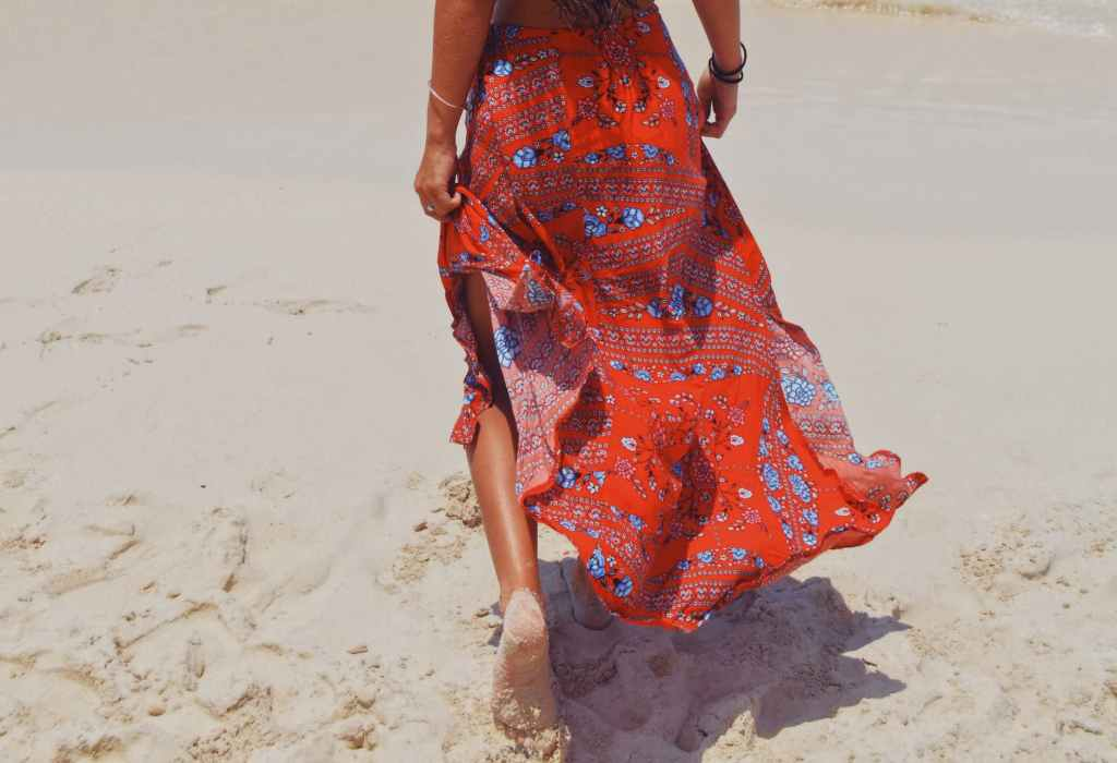 Woman walking on the beach in a colorful skirt
