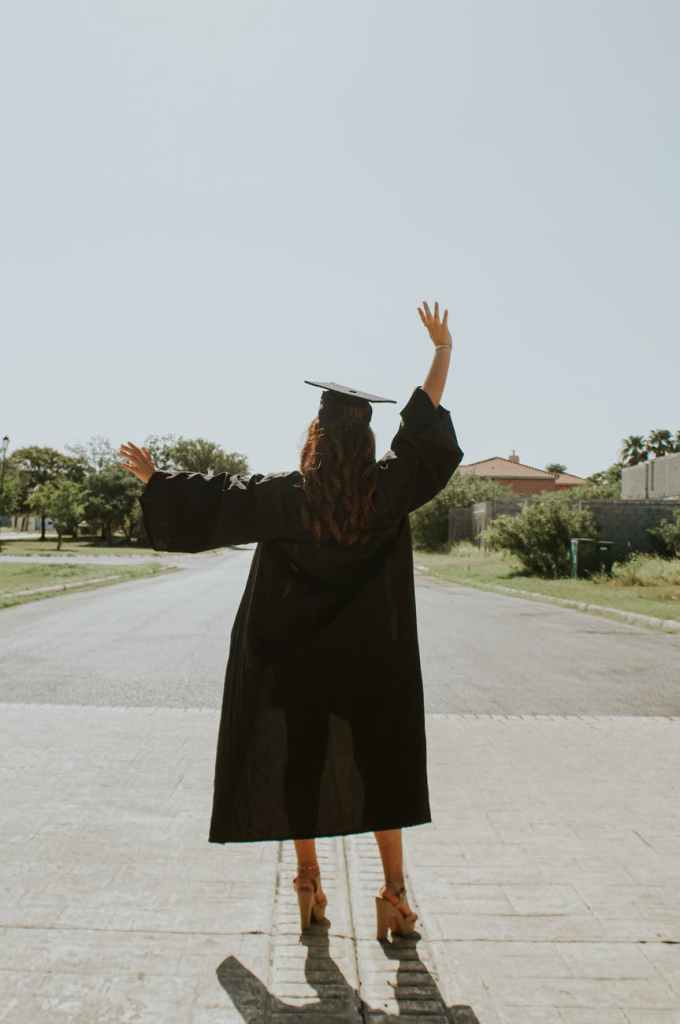Young girl with cap and gown on, waving