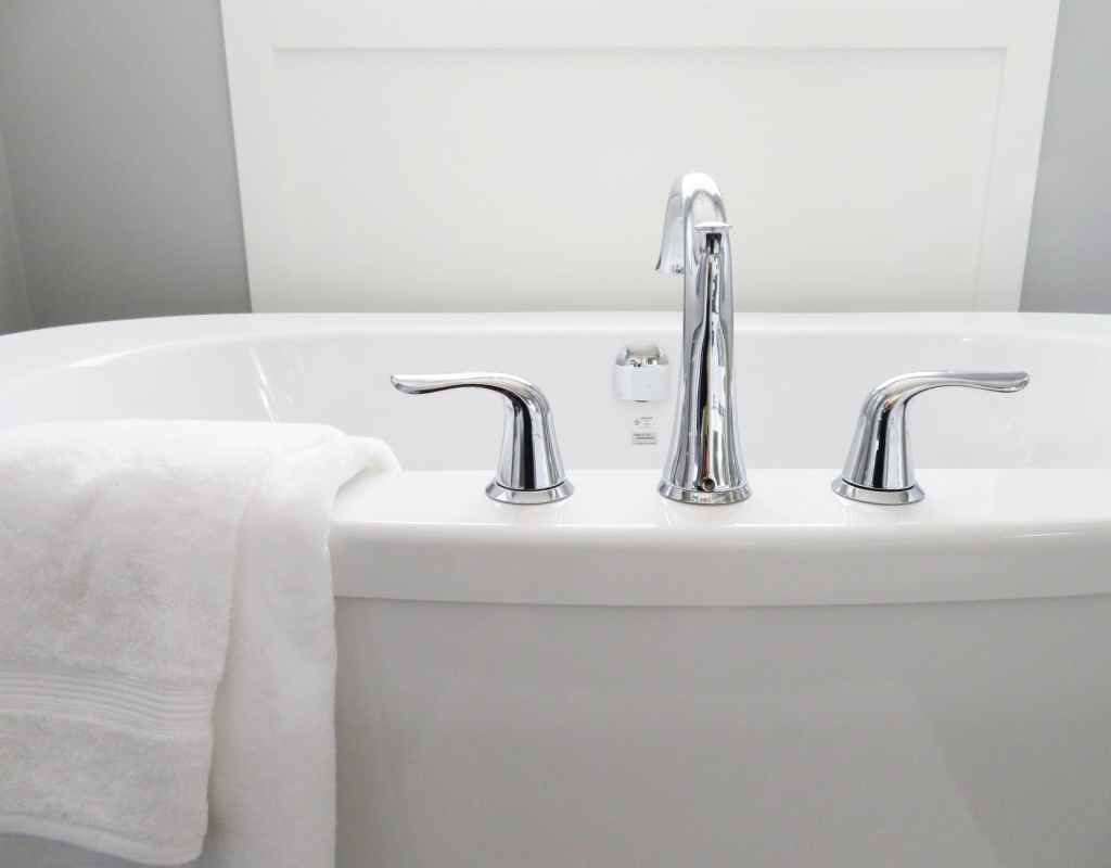 White tub with chrome faucet and white towel