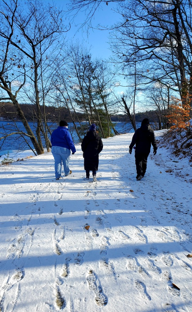 3 women walking along a snow covered path