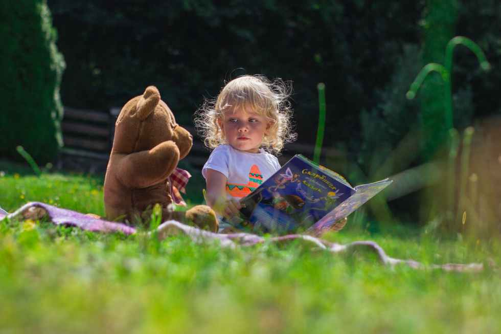 little girl reading a book to a teddy bear